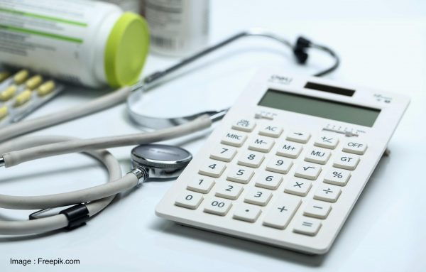 calculator, stethoscope and medicine bottles on white background